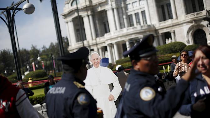 Police walk past a cardboard cut-out of Pope Francis outside the Museum of Fine Arts in Mexico City