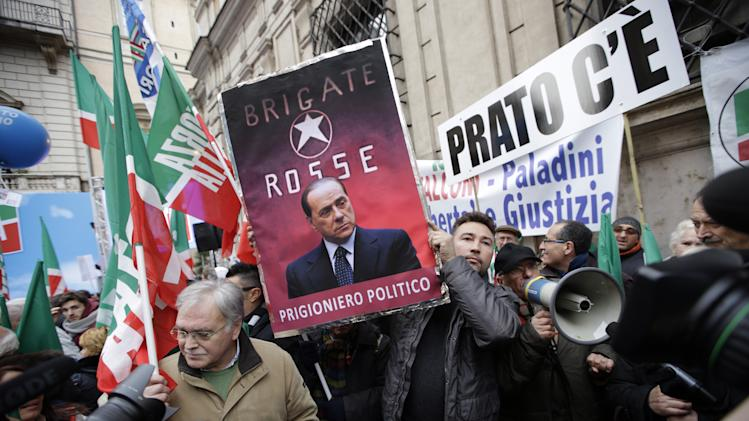 """A supporter displays a poster depicting Italian Former Premier Silvio Berlusconi on the backdrop of former Italian terrorist group Brigate Rosse (Red Brigates) and reading in Italian """"Political prisoner"""", while he waits for Berlusconi's speech at a rally organized outside of his Rome residence, Wednesday, Nov. 27, 2013. The Italian Senate has begun debating whether to kick Silvio Berlusconi out of Parliament following his tax fraud conviction. The vote is scheduled later in the day and most analysts expect he will lose his seat. Berlusconi fans massed in front of Berlusconi's Rome palazzo for a planned rally that analysts say is essentially the start of Italy's next electoral campaign. (AP Photo/Andrew Medichini)"""