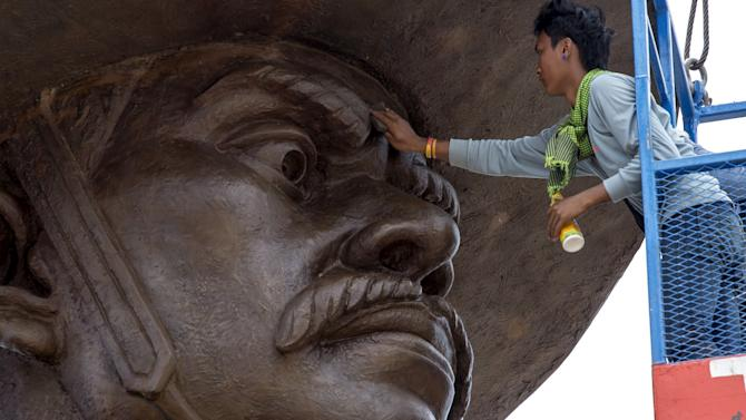 A labourer works on a giant bronze statue of former King Taksin at Ratchapakdi Park in Hua Hin, Prachuap Khiri Khan province