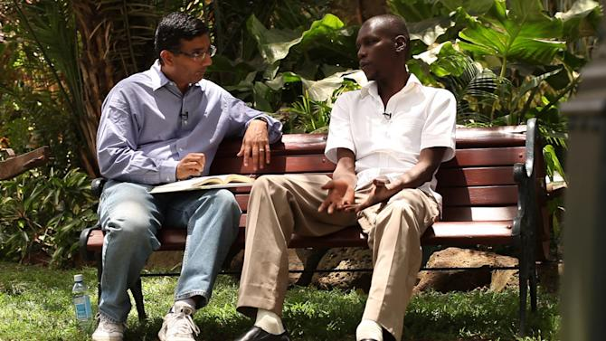 """In this publicity image released by Rocky Mountain Pictures, director Dinesh D'Souza, interviews George Obama in his film, """"2016: Obama's America."""" D'Souza has been indicted in New York on charges he violated campaign finance laws. Federal prosecutors announced the charges Thursday, Jan. 23, 2014 against D'Souza, and say he'll be arraigned Friday on charges he directed $20,000 in illegal contributions to be made in the New York Senate race in 2012. (AP Photo/Rocky Mountain Pictures, File)"""