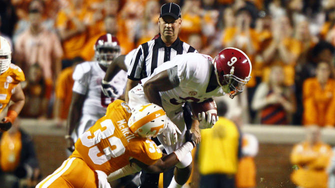 Alabama wide receiver Amari Cooper (9) runs for a yardage as he is hit by Tennessee defensive back LaDarrell McNeil (33) in the first quarter of an NCAA college football game Saturday, Oct. 25, 2014, in Knoxville, Tenn. (AP Photo/Wade Payne)