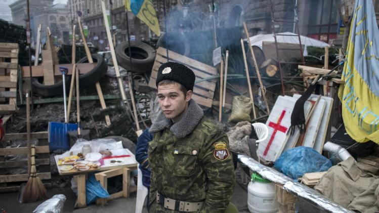 An Ukrainian pro-EU demonstrator is seen near a barricade during a rally in Independence Square in central Kiev