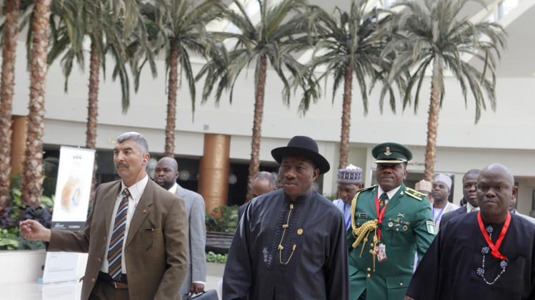 Nigerian president Goodluck Jonathan, center, is surrounded by security and members of his delegation at the 12th summit of the Organization of Islamic Cooperation in Cairo, Egypt, Wednesday, Feb. 6, 2013.  The summit aims to address a wide range of issues including, Palestinian statehood, the Syrian crisis, poverty in the Islamic world and conflicts in Afghanistan and Somalia. (AP Photo/Amr Nabil)