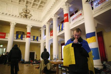 A protester wrapped in an Ukrainian flag uses his tablet inside Kiev's City Hall, now an organisational hub for protesters who have occupied the building