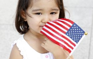 Shahi holds onto a U.S. flag during a special naturalization…