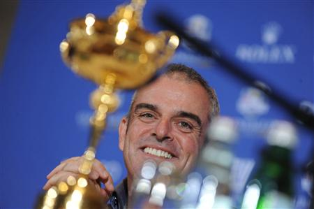 Paul McGinley of Ireland smiles near the Ryder Cup during a news conference after being named the European Ryder Cup captain at the St. Regis in Saadiyat Islands in Abu Dhabi