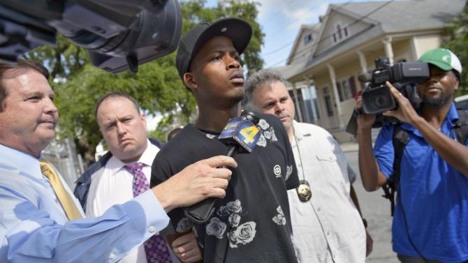 Shawn Scott, 24, a suspect in the Mother's Day parade shooting  is led out of the New Orleans 5th District Police Station, Thursday, May 16, 2013 in New Orleans. Shawn and Akein Scott. two brothers with a history of drug arrests and suspected ties to a neighborhood gang each face 20 counts of attempted second-degree murder in a shooting spree that brought a sudden bloody end to a neighborhood Mother's Day parade. (AP Photo/Matthew Hinton)