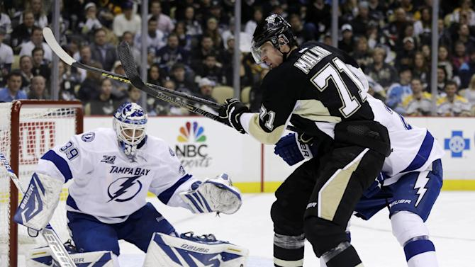 Pittsburgh Penguins center Evgeni Malkin (71) can't get to the puck while being defended by Tampa Bay Lightning defenseman Matt Carle (25) in front of Tampa Bay Lightning goalie Anders Lindback (39) in the second period of an NHL hockey game in Pittsburgh, Monday, March 4, 2013. (AP Photo/Gene J. Puskar)