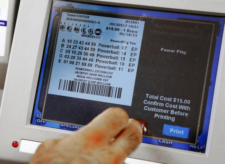 A clerk dispenses a Powerball Lottery ticket in Oklahoma City, Friday, May 17, 2013. Powerball officials say the jackpot has climbed to an estimated $600 million, making it the largest prize in the game's history and the world's second largest lottery prize.(AP Photo/Sue Ogrocki)