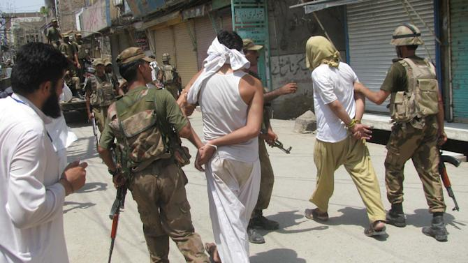 Pakistan army soldiers escort alleged suspects arrested during a crackdown operation against militants in Bannu, Pakistan, Monday, July 16, 2012. Pakistani Taliban attacked an office of the security force's intelligence agency in the country's northwest on Monday, taking several hostages before police stormed the building and ended the siege, police said. (AP Photo/Ijaz Mohammed)