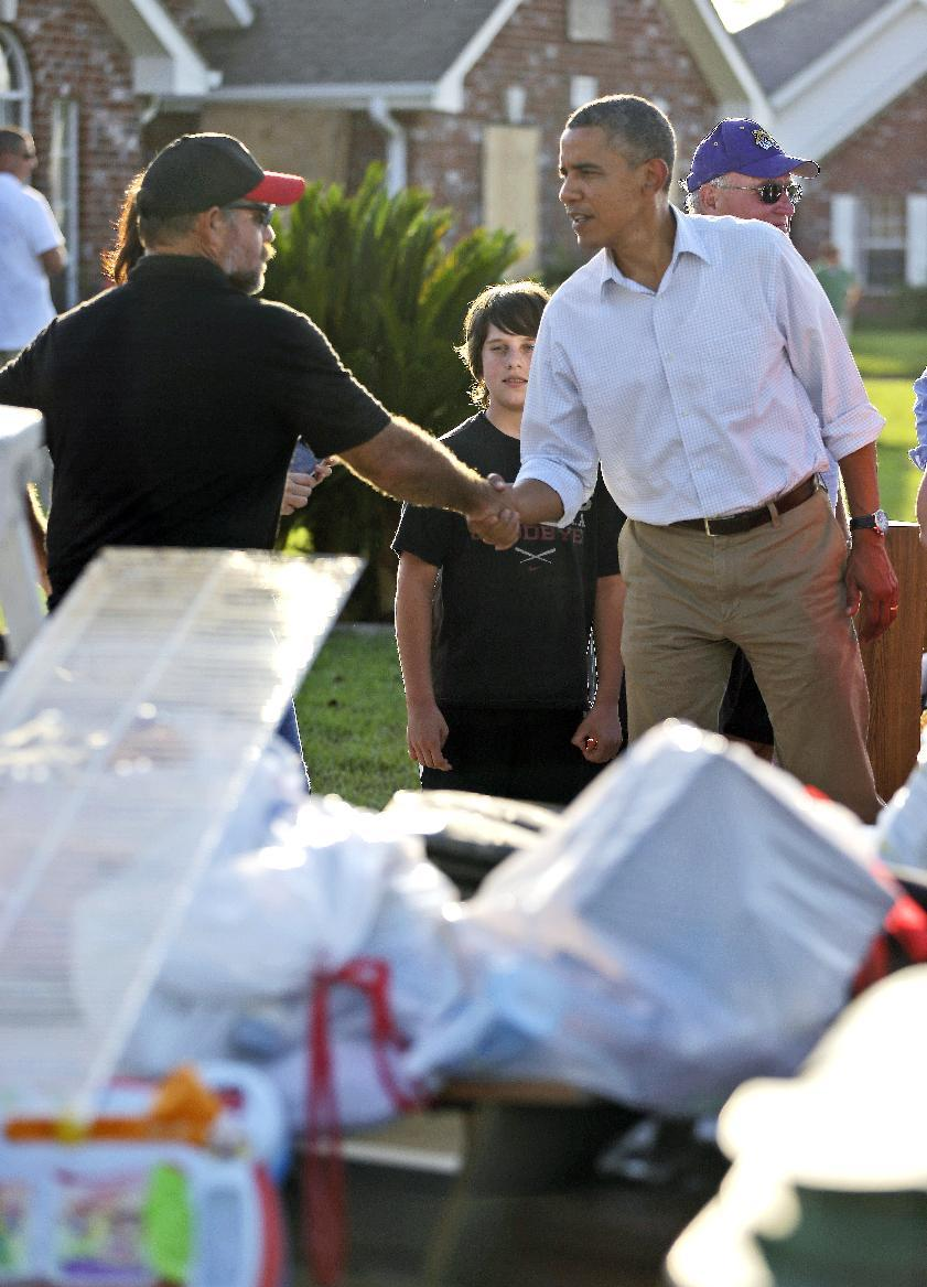 President Barack Obama, right, greets a local resident as he tours the Bridgewood neighborhood in LaPlace, La., in Saint John the Baptist Parish, as he surveys the ongoing response and recovery efforts to Hurricane Isaac, Monday, Sept. 3, 2012. (AP Photo/Pablo Martinez Monsivais)