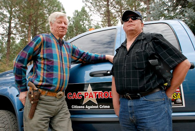 In this Oct. 12, 2012, photo, Sam Nichols, left, and Glenn Woodbury pose in front of Woodbury's pickup in O'Brien, Ore. The two men are part of a newly-formed neighborhood watch that does armed patrols around the rural area to deter crime since budget cutbacks have left the Josephine County Sheriff's Office with just three patrol deputies and limited jail space. (AP Photo/Jeff Barnard)