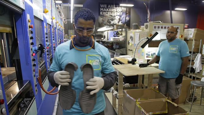 In this photo taken Wednesday, July 1, 2015, Joao Rodrigues, left, removes a pair of newly formed midsoles for the New Balance proposed 950v2 sneaker, that has passed military testing, from an IMEVA oven as Loyd Johnson looks on at one of company's manufacturing facilities in Boston. New Balance is pressing the Pentagon to buy American-made footwear for the troops instead of sneakers from rival Nike that are made in China. (AP Photo/Stephan Savoia)