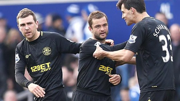 Shaun Maloney celebrates with his Wigan team-mates after scoring against QPR (AFP)