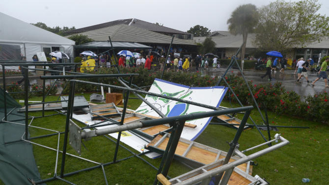 Spectators make their way past a scoreboard that toppled over behind the first tee after a severe thunderstorm passed through during the final round of the Arnold Palmer Invitational golf tournament in Orlando, Fla., Sunday March 24, 2013.(AP Photo/Phelan M. Ebenhack)