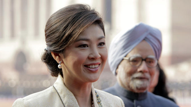 FILE - In this Jan. 25, 2012 file photo, Thai Prime Minister Yingluck Shinawatra talks to the media with Indian Prime Minister Manmohan Singh, right, during a ceremonial reception at the Presidential Palace in New Delhi, India. As she marks a year in office this weekend as Thailand's first female prime minister, Yingluck's biggest boast could be about what hasn't happened during that time: a return to the chaos that has wracked the country for much of the past six years. (AP Photo/Gurinder Osan, File)