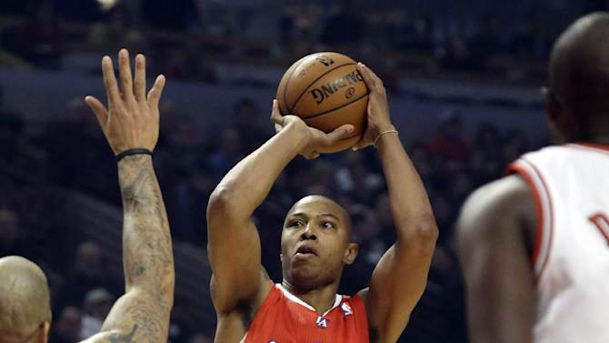 Los Angeles Clippers forward Caron Butler (5) shoots between Chicago Bulls forward Carlos Boozer, left, and Luol Deng during the first half of an NBA basketball game, Tuesday, Dec. 11, 2012, in Chicago. (AP Photo/Charles Rex Arbogast)