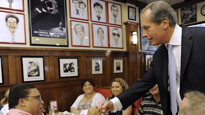 Lt. Gov. David Dewhurst, right, fist bumps Jason Carter at a deli Tuesday, July 31, 2012, in Houston. Dewhurst faces former Texas Solicitor General Ted Cruz in the Republican primary runoff election for U.S. Senator. Carter had jokingly handed Dewhurst his lunch tab and Dewhurst quickly gave it back. (AP Photo/Pat Sullivan)