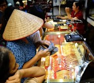 Customers buy and sell gold at a local gold shop in Hanoi. Officials are trying to dampen the gold fever by bringing the trade back into their hands, almost two decades after they formally legalised the already-common practice of private gold ownership and trading