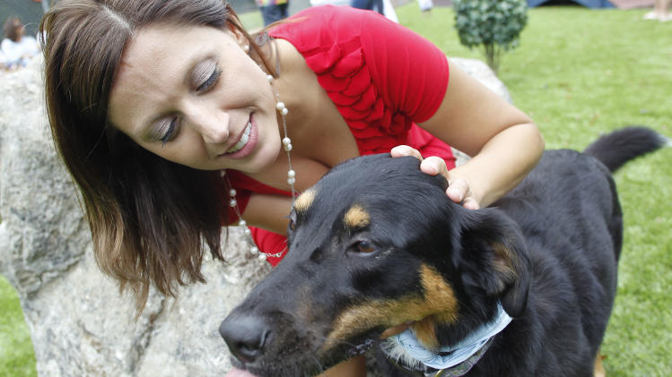 Jenny Wilson hugs her dog Honey Belle at the new Alabama Dream Dog Park in Alabaster, Ala., Thursday, July 12, 2012. The $500,000 renovation creates a dog park with many unique features that include: custom-designed water splash pads to keep dogs cool during hot Alabama summers; a fetch football field with fire hydrant goal posts; a hill that dogs and owners can climb together to enjoy the view; a doggie wash station; and an adventure path with tunnels and agility hoops, among others. (AP Photo/Dave Martin)