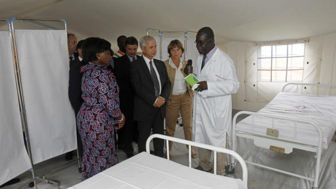 President of the French National Assembly Claude Bartolone talks with a health worker during a visit at the Ebola treatment unit at the main hospital of Yopougon in Abidjan