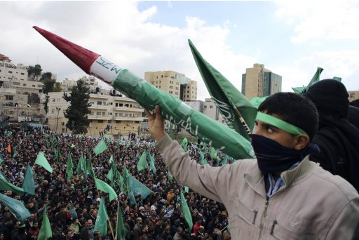 Palestinian youth holds model of Hamas-made rocket during rally in West Bank city of Hebron