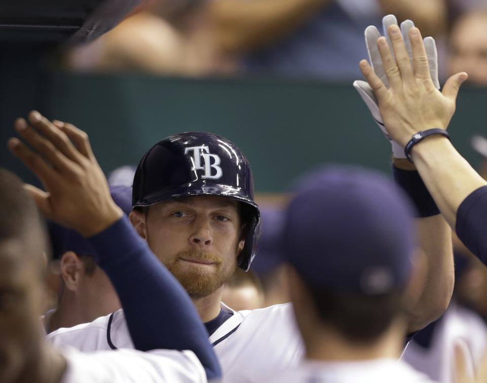 Tampa Bay Rays' Ben Zobrist high-fives teammates in the dugout after his fourth-inning home run off Baltimore Orioles starting pitcher Wei-Yin Chen during a baseball game, Monday, Oct. 1, 2012, in St. Petersburg, Fla. (AP Photo/Chris O'Meara)