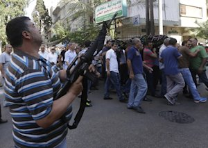 A Lebanese Shiite gunman fires by his rifle as mourners, …