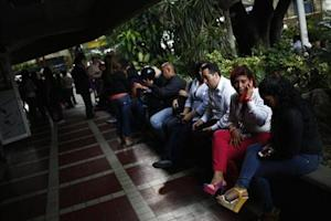 People sit outside a shopping mall during a massive blackout in Caracas