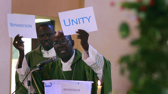 South Sudanese Catholic Archbishop Paulino Lukudu holds up mock ballots during a service attended by President Salva Kiir in  Juba, Southern Sudan, Sunday  Jan. 16, 2011. The Southern Sudan's president on Sunday offered a prayer of forgiveness for northern Sudan and the killings that occurred during a two-decade civil war, as the first results from a weeklong independence referendum showed an overwhelming vote for secession. About four million  Southern Sudanese voters cast their ballots  in a weeklong referendum on independence that is expected to split Africa's largest nation in two.(AP Photo/Jerome Delay)