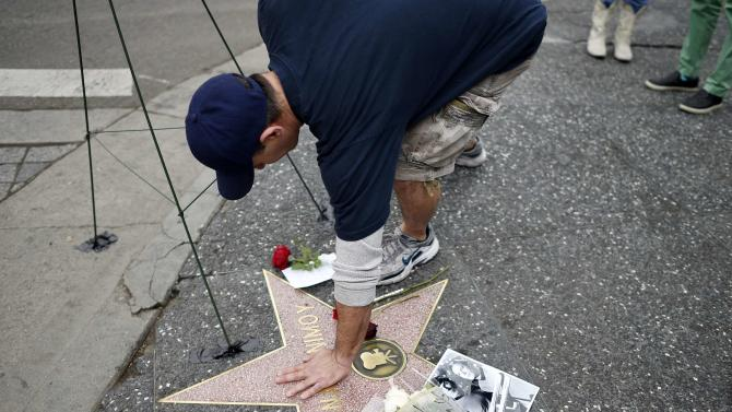 A fan touches the Hollywood Walk of Fame star of actor Leonard Nimoy, which is adorned with flowers, on Hollywood Boulevard in Los Angeles, California
