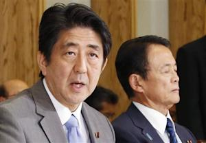 Japan's Prime Minister Shinzo Abe, seated with Finance Minister Taro Aso, speaks during the Council on Economic and Fiscal Policy meeting in Tokyo