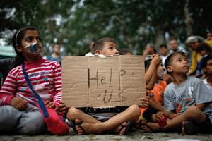 A child holds up a sign as migrants stage a protest …