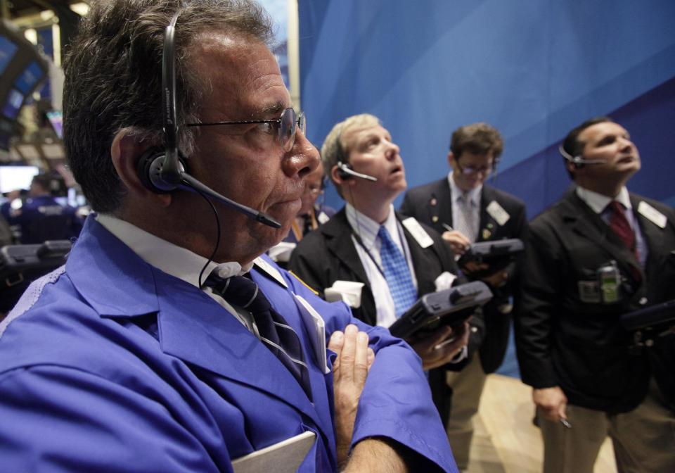 Sal Suarino, left, works with fellow traders on the floor of the New York Stock Exchange Monday, Aug. 1, 2011. (AP Photo/Richard Drew)