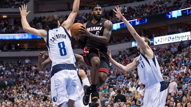 Miami Heat small forward LeBron James drives to the basket past Dallas Mavericks point guard Jose Calderon (8) and power forward Dirk Nowitzki (41) (Reuters)