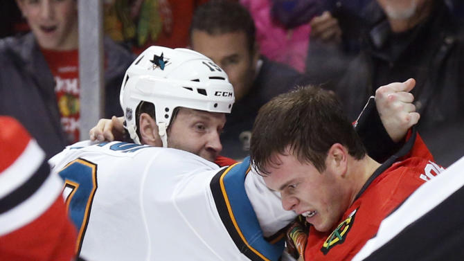 San Jose Sharks center Joe Thornton, left, and Chicago Blackhawks center Jonathan Toews fight during the first period of an NHL hockey game Friday, Feb. 15, 2013, in Chicago. (AP Photo/Charles Rex Arbogast)