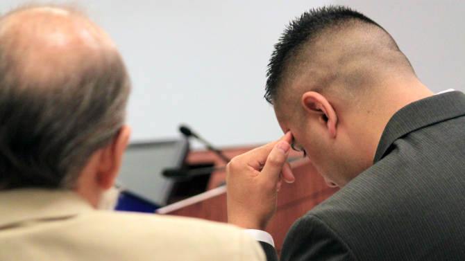 Former Albuquerque Police Officer Levi Chavez, right, sits with his attorney David Serna before his trial begins in state district court in Bernalillo, N.M., on Monday, June 10, 2013. Chavez is accused accused of killing his 26-year-old wife in the couple's home south of Albuquerque. His defense attorney disputes the allegations, saying the evidence points to suicide. (AP Photo/Susan Montoya Bryan)