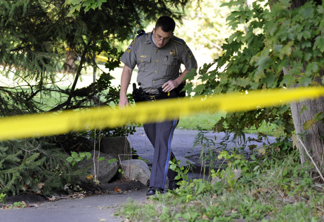 State Trooper Matt Losh emerges from the backyard of a home in New Fairfield, Conn., where a fatal shooting took place, Thursday, Sept. 27, 2012. Police say Jeffrey Giuliano shot a masked teenager in self-defense during what appeared to be an attempted burglary early Thursday morning, then discovered that he had killed his son, Tyler. (AP Photo/The News-Times, Carol Kaliff)