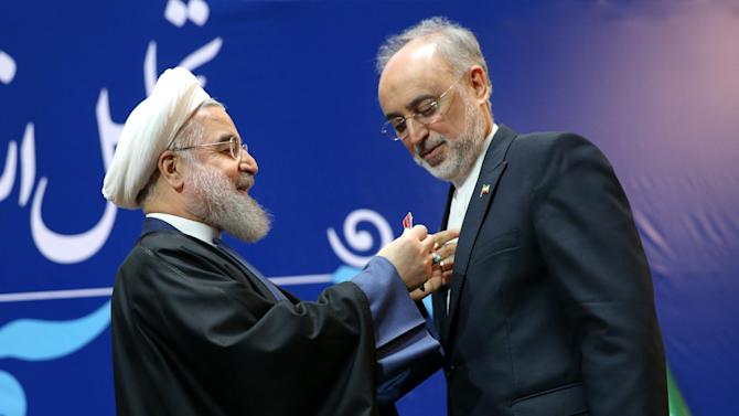 "Iranian President Hassan Rouhani, left, awards a medal to Vice President and head of Iran's Atomic Energy Organization, Ali Akbar Salehi, in Tehran, Iran, Monday, Feb. 8, 2016. Iran awarded medals of honor on Monday to its nuclear negotiators who helped clinch a landmark deal with world powers last year. President Hassan Rouhani awarded the ""Medal of Merit"" to Foreign Minister Mohammad Javad Zarif and the ""Medal of Courage"" to Defense Minister Hossein Dehghan and Salehi. (AP Photo/Ebrahim Noroozi)"