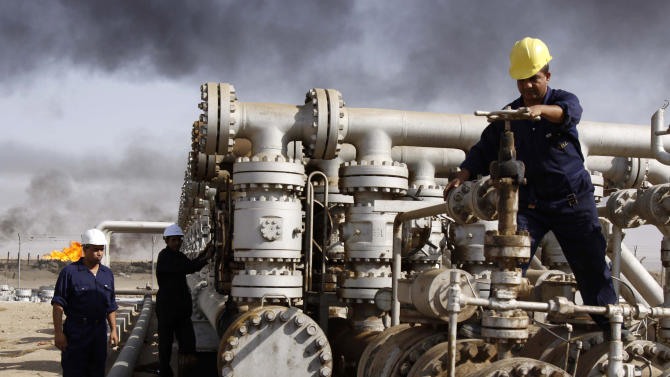 FILE - In this Dec. 13, 2009 file photo, Iraqi workers are seen at the Rumaila oil refinery, near the city of Basra, 340 miles (550 kilometers) southeast of Baghdad, Iraq. Iraq's rapidly expanding oil production is likely to complicate OPEC's efforts to influence world prices as the country re-emerges as a major player after 20 years on the sidelines due to sanctions and strife. (AP Photo/Nabil al-Jurani, File)