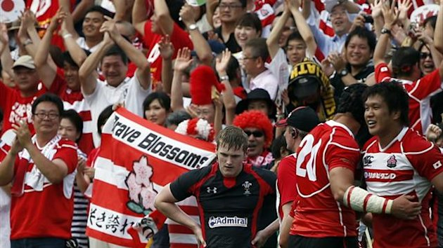 Wales' Dafydd Howells (C) reacts as Japan's Takashi Kikutani (R) and Justin Ives celebrate after Wales is defeated by Japan during their international rugby test match in Tokyo June 15, 2013 (Reuters)