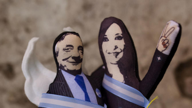 """A shop worker at the Bicentennial Museum shows dolls of Argentian's former President Nestor Kirchner, left, and his wife President Cristina Fernandez in Buenos Aires, Argentina, Wednesday, Nov. 21, 2012.  A documentary film titled """"Nestor Kirchner"""" hits the theaters on Thursday, the latest example of an ongoing effort to exalt the late president's memory, seeking to match the level of Juan Domingo Peron.  Streets, hospitals, tunnels and even a soccer tournament is named after Nestor Kirchner, who served as president from 2003 to 2007 and died at the age of 60 on Oct. 27, 2010. (AP Photo/Natacha Pisarenko)"""