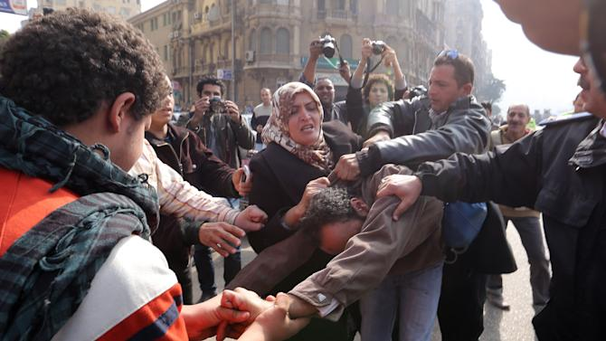 Supporters of an anti-Muslim Brotherhood group hit a supporter of ousted Egyptian President Mohamed Mursi and the Muslim Brotherhood at Talaat Harb Square in Cairo,