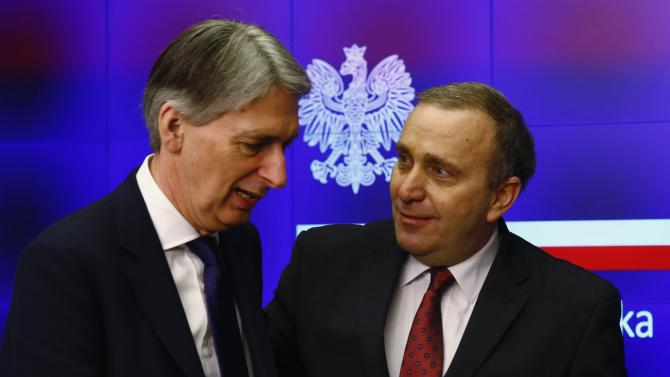 Poland's Foreign Minister Schetyna looks at Britain's Foreign Secretary Hammond as they leave after news conference at the Foreign Ministry in Warsaw