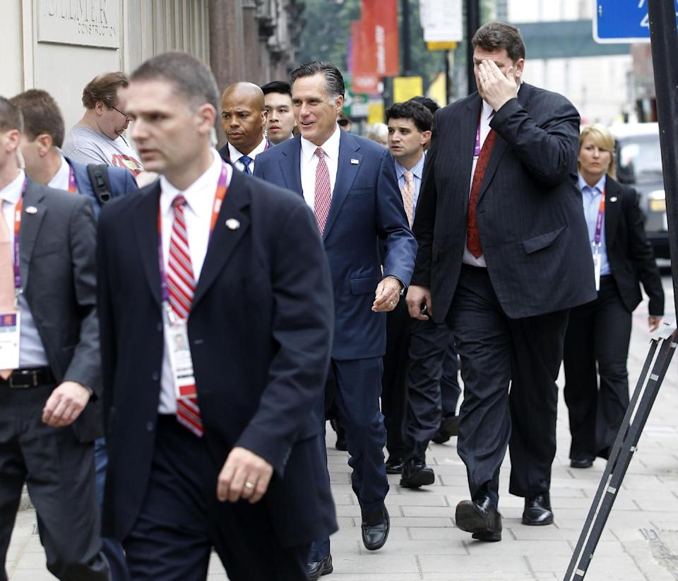 Avoiding a traffic jam, Republican presidential candidate, former Massachusetts Gov. Mitt Romney walks down Grosvenor Place in London to meet Ireland's Prime Minister Enda Kenny at the Embassy of Ireland in London, Friday, July 27, 2012. (AP Photo/Charles Dharapak)