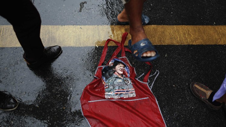 Protesters step on a picture of the Prime minister Yingluck Shinawatra as they march through Bangkok's shopping district