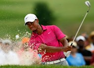 Tiger Woods plays a shot from a sand trap on the ninth hole during the third round of the WGC-Bridgestone Invitational on August 4. Woods broke par for the first time this week, shooting a two-under 68
