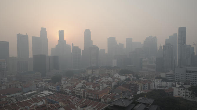 In this picture taken on Thursday, June 20, 2013, the Central Business District of Singapore is shrouded by unhealthy levels of haze. Air pollution in Singapore has soared to record heights for a third consecutive day Friday, June 21, as Indonesia prepared planes and helicopters to battle raging fires blamed for hazardous levels of smoky haze in three countries. The blazes in peat swamp forests on Indonesia's Sumatra island have sent massive plumes of smog across the sea to neighboring Singapore and Malaysia. (AP Photo/Joseph Nair)