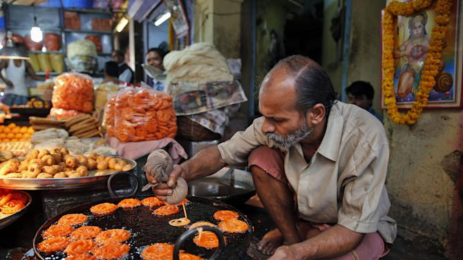 "An Indian vendor prepares a traditional sweet ""Imarti"" at his shop in old market in Allahabad, India, Friday, Feb. 27, 2015. The Economic Survey, an annual report on the state of Asia's third-largest economy, said Friday that India's economy will grow more than 8 percent in the upcoming financial year, which would make it the world's fastest growing, surpassing China. (AP Photo/Rajesh Kumar Singh)"