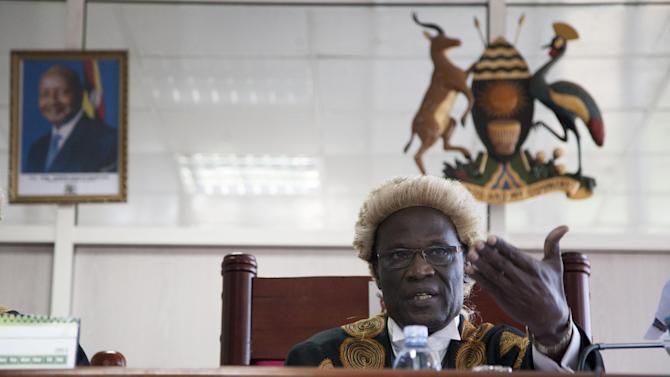 A photo of Uganda's president hangs on the wall, left, as Judge, Stephen Kavuma reads the verdict at Uganda's Constitutional court, Friday, Aug.1, 2014. A Ugandan court has invalidated an anti-gay bill signed into law earlier this year, saying it was illegally passed and is therefore unconstitutional. The panel of five judges on the East African country's Constitutional Court said the speaker of parliament acted illegally when she went ahead to allow a vote on the measure despite at least three objections over lack of quorum. (AP Photo/Rebecca Vassie)